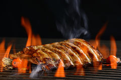 Grilled pork ribs. With vegetable on the flaming grill Stock Photo