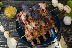 Grilled pork ribs with vegetables and spices on a wooden background. Side view stock photo