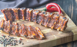 Grilled pork ribs. On the wooden board Stock Photos