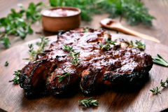 Grilled pork ribs. On wooden board, shallow depth of field Royalty Free Stock Images