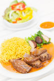 Grilled pork ribs with yellow noodle and vegetable on white table. Stock Photo