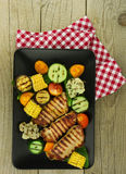 Grilled pork with roasted vegetables on black dish. BBQ Royalty Free Stock Photo