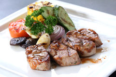 Grilled pork with roasted vegetables on white dish Stock Photos