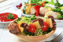 Grilled pork skewer and spring salad Royalty Free Stock Image