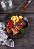 Grilled pork spare ribs with fries on black plate. Roasted sliced barbecue ribs. stock images