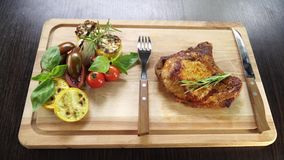 Grilled pork steak on the bone with vegetables on a wooden board with kitchen appliances. 4k video stock video