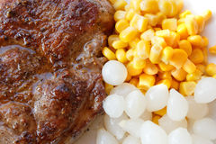Grilled pork steak with corn and small onions stock image