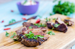 Grilled pork steak cutting on chopping board with vegetables around Royalty Free Stock Photo