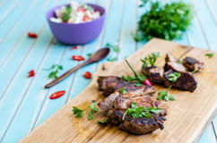 Grilled pork steak cutting on chopping board with vegetables Royalty Free Stock Photography