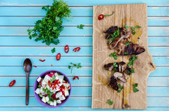 Grilled pork steak cutting on chopping board with vegetables Stock Images