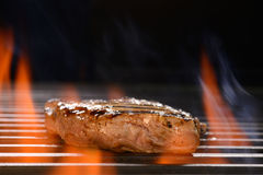 Grilled pork steak. On the flaming grill Royalty Free Stock Image