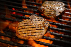 Grilled pork steak. On the flaming grill Stock Image