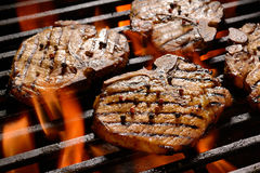 Grilled pork steak. On the flaming grill Stock Photos