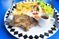 Grilled pork steak. With french fries on table Royalty Free Stock Photo