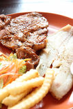 Grilled pork steak with french fries and toast. Royalty Free Stock Photos