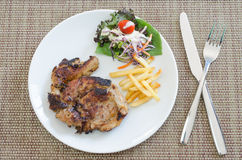Grilled pork steak with french fries and vegetables Royalty Free Stock Photo