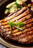 Grilled pork steak with fresh salad. Close up. Vertical. royalty free stock image