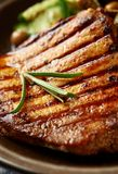 Grilled pork steak with fresh salad. Close up. Vertical. Grilled pork steak with cucumber, green olives and capers. Vertical Stock Photos
