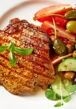 Grilled pork steak with fresh salad. Top view. Vertical Stock Images