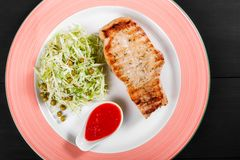 Grilled pork steak with green salad of cabbage and peas in plate on dark background. Hot Meat Dishes. Top view, flat lay stock photography