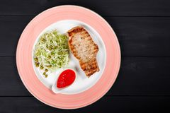 Grilled pork steak with green salad of cabbage and peas in plate on dark background. Hot Meat Dishes. Top view, flat lay royalty free stock images