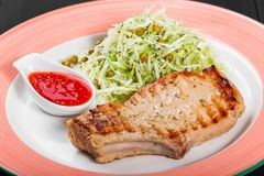 Grilled pork steak with green salad of cabbage and peas in plate on dark background. Hot Meat Dishes. Top view, flat lay stock photo