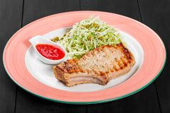 Grilled pork steak with green salad of cabbage and peas in plate on dark background. Hot Meat Dishes. Top view, flat lay stock images