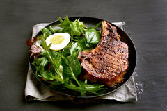 Grilled pork steak with green salad. Grilled pork steak and green salad, close up view royalty free stock images