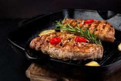 Grilled pork steak in grill pan stock photography