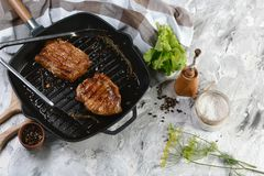 Grilled pork steak in an iron pan with herbs and spices. Food concept.  stock images