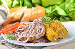 Grilled pork steak meal. Hot, tasty, delicious grilled pork steak meal with corn on the cob, onions, red peppers and lettuce and bread in the background stock image