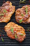 Grilled pork steak, pork neck with the addition of herbs and spices on the grill plate, top view. Grilled meat, bbq, barbecue grill stock images