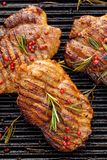 Grilled pork steak, pork neck with the addition of herbs and spices on the grill plate, top view. Grilled meat, bbq, barbecue grill stock photo