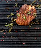 Grilled pork steak, pork neck with the addition of herbs and spices on the grill plate, top view. Grilled meat, bbq, barbecue grill royalty free stock image