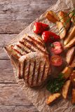 Grilled pork steak with potatoes on paper top view vertical Royalty Free Stock Photos