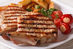 Grilled pork steak with potatoes and vegetables on a plate, macr Stock Photo