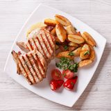 Grilled pork steak with potatoes and vegetables top view Stock Photos