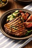 Grilled Pork Steak with Salad. Vertical. Grilled Pork Steak with tomatoes, cherry tomatoes, cucumber, kalamata olives, green olives and capers. Concept for royalty free stock images