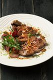 Grilled pork steak with spices, rosemary, arugula on a white pla. Te on a dark background royalty free stock images