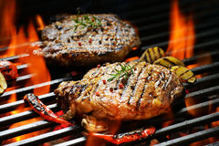 Grilled pork steak. With vegetable on the flaming grill Stock Photos