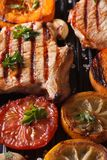 Grilled pork steak and vegetables on the grill. Vertical macro Royalty Free Stock Photography