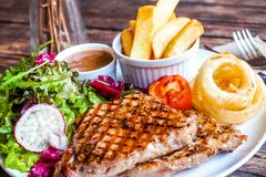 Grilled pork steak with vegetables salad and french fries royalty free stock image