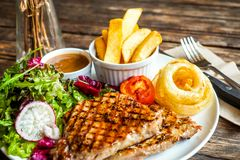 Grilled pork steak with vegetables salad and french fries royalty free stock photo