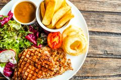 Grilled pork steak with vegetables salad and french fries stock photos