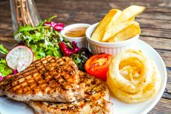 Grilled pork steak with vegetables salad and french fries stock photography