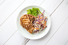 Grilled pork steak. With vegetables salad on a wooden board Royalty Free Stock Photo