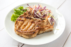 Grilled pork steak. With vegetables salad on a wooden board Stock Photo
