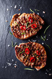Grilled pork steaks with chili peppers and spices royalty free stock photos