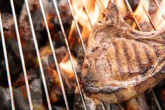 Grilled pork steaks over flames on the grill. Stock Photo