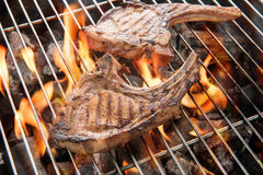 Grilled pork steaks over flames on the grill. Stock Image